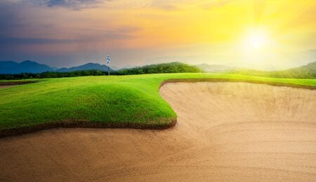 green golf course with sand bunker at sunset and sunbeam