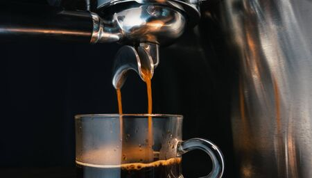 Barista making an espresso shot coffee water pouring from the blind filter tow way by automatic Espresso Machine into cup glass, close-up Stock fotó