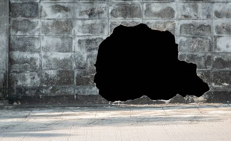 Old concrete brick wall broken and black hole for use background