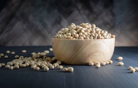 close up of dried soybeans in a wooden bowl on table with dark background