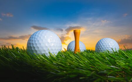 close up the golf ball and tee pegs on the green background with sunset