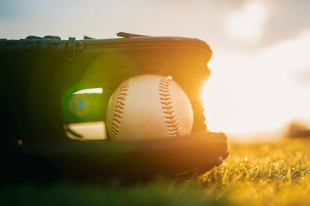 Baseball in glove in the lawn at sunset in the evening day with sun ray and lens flare light
