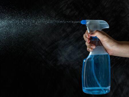close up of female hand holding foggy spray bottle and spraying on dark background Standard-Bild