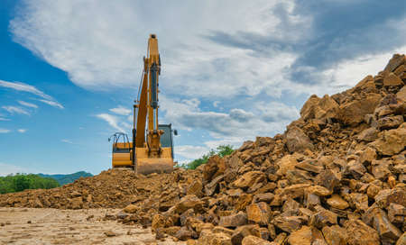 Backhoe is working on pile of stones at construction site