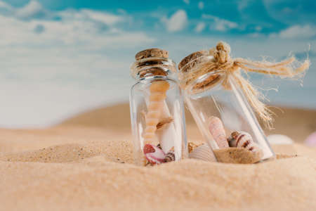 View of the sandy beach and shells in two glass jar on sand and summer beach