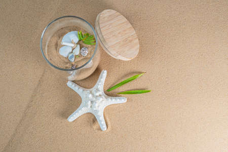 top view of sand beach with sea star and shells in glass jar