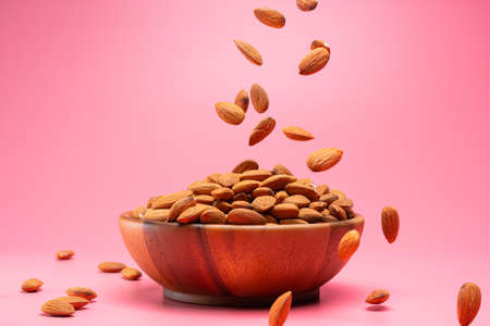 Almond dry seeds in a wooden bowl and with seeds falling on the pink background Reklamní fotografie