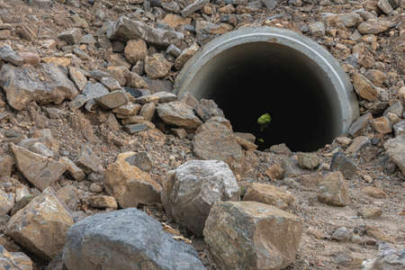 Concrete drain pipe under the ground and rocks 写真素材