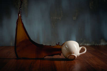 hot coffee cup spilling onto the wooden floor and coffee water splash on dark background 写真素材