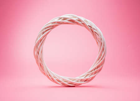 white wreath from vine isolated on pink background