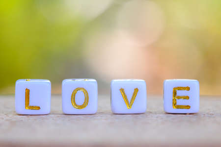 LOVE words made small plastic cubes blocks on wooden table in nature background, concepts of love