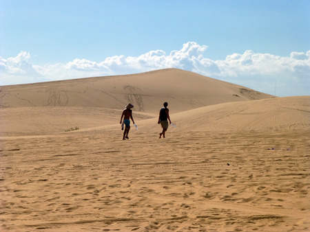 Two people walk on the Sands. Desert on a background of blue sky. The hot summer sun. Horizontal photo.