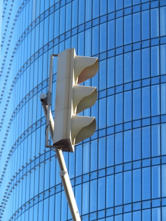 Traffic light on the background of a glass building in the city. White on a blue background.