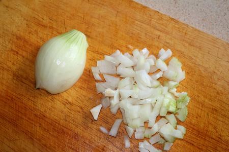 Chopped onions on wooden cutting board. Chopped fresh, raw onion.