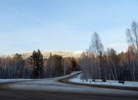 Beautiful winter road running through the snowy woods. Banco de Imagens