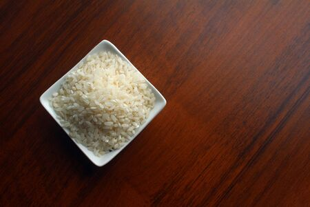 White Bowl with grains of white rice on a wooden table, top view. Banco de Imagens