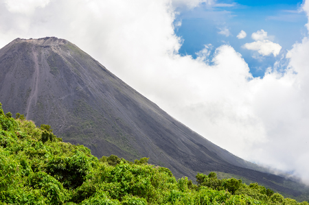 active volcano: The perfect peak of the active and young Izalco volcano seen from a view point in Cerro Verde National Park in El Salvador. Nearly covered with thick white clouds.