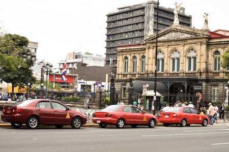 san jose: San Jose, Costa Rica - August 18, 2015: Classic red taxi cars are parked in front of the National Theater of Costa Rica, the main tourists attraction of the capital, on August 18, 2015 in San Jose, Costa Rica