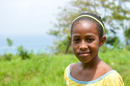 creole: Great Corn Island, Nicaragua - July 6, 2015:  Beautiful Creole girl poses and smiles wearing funky colors on July 6, 2015 in Great Corn Island, Nicaragua.