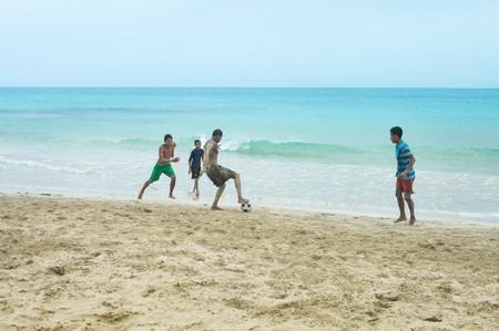creole: Great Corn Island, Nicaragua - July 10, 2015:  Local teens play football on the beach by the Caribbean in Great Corn Island, Nicaragua