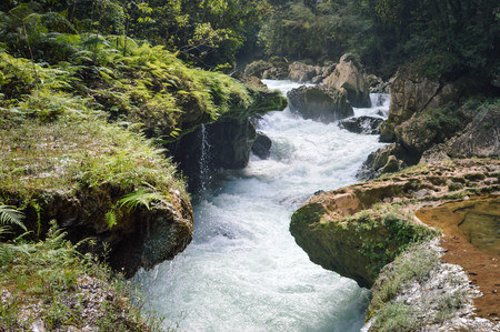 The close up of the Cahabon river going underground and the small waterfalls falling off the limestone bridges in Semuc Champey, Alta Verapaz region, Guatemala