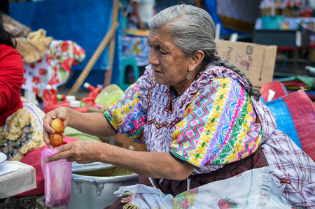 Quetzaltenango, Guatemala - February 8, 2015: Maya woman sells sweet deep fried bunuelos at a local food market in Xela, Guatemala Editorial