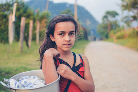 seller: Pena Blanca, Honduras - May 6, 2015: Local girl carries a pot with tortillas to sell in the evening hours in a small village of coffee growers in Santa Barbara National Park. Honduras