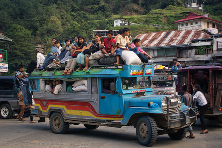 Banaue, Philippines - June 17, 2009: Typical Jeepney overloaded with passengers near Banaue, North Luzon, Philippines. Jeepneys are both cheap public transportation and the symbol of Philippine culture and art Stock Photo - 89239592