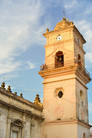 rebuilt: Granada, Nicaragua - July 25, 2015:  Tourists visit the clock tower of the beautiful Iglesia de la Merced in Granada, Nicaragua on sunset. This church was first built in 1539, then rebuilt in 1780 Editorial