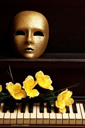 theatre masks: gold mask and yellow flower on a piano