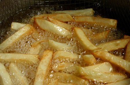 french fries in hot oil Imagens