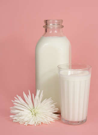 bottle and glass of milk on pink background