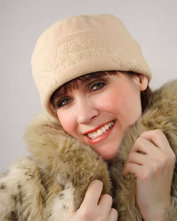 factitious: woman wearing a beige hat and factitious fur coat Stock Photo