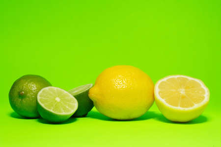 fresh lemon and lime on green background