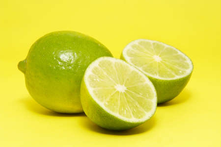 lemon fresh lime on yellow background Imagens