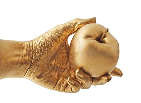 gold hand holding and apple