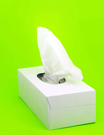 white box of facial tissue on green background