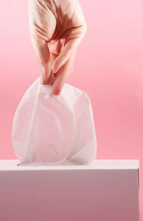 female hand pulling white facial tissue from a box, pink background