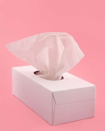 white box of facial tissue on pink background Stock Photo