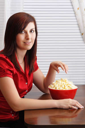 young woman at table, with popcorn in a red bowl photo