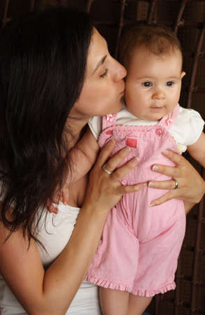 mother kissing her baby girl, black background