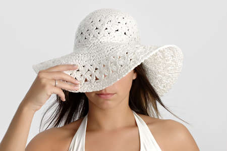 young happy woman hiding behind a white hat Stock Photo