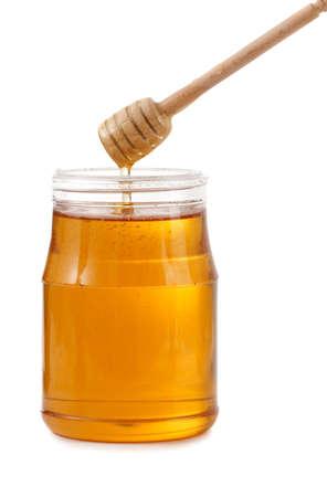 jar of fresh honey with wood stick, white background