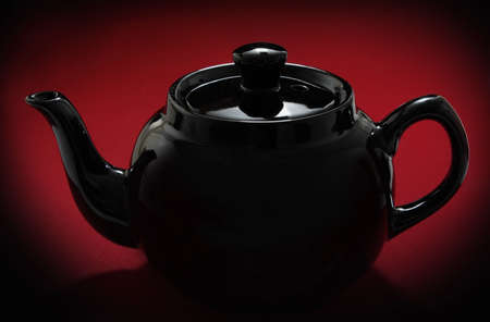 red teapot over red background