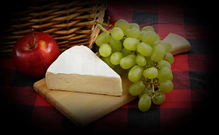 cheese, grape and apple on wood plank, near wicker basket