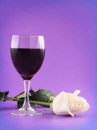 glas rode wijn en witte roos