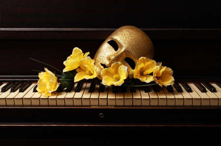 gold mask and yellow flower on a piano