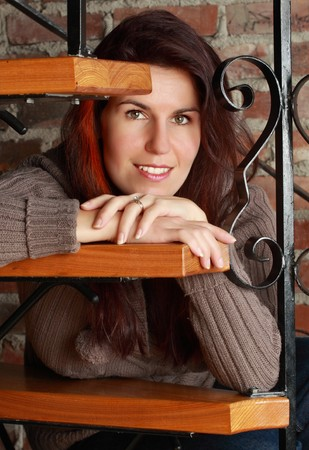 beautiful woman sitting on staircase, brick wall background photo