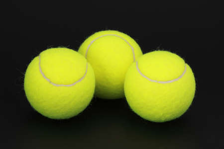 three yellow new tennis ball, black background