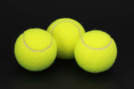 three yellow new tennis ball, black background